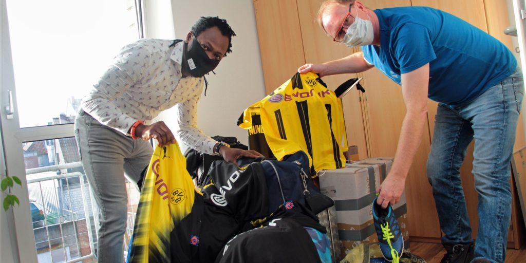 Erfolgreiche Zwischenbilanz: Toni Tuklan (l.) und Dietmar Wurst aus Werne arbeiten sich durch den Berg an gespendeten Trikots und Sportartikeln. Im März sollen die ausrangierten Trikots, etwa vom BVB, nach Afrika geschickt werden.