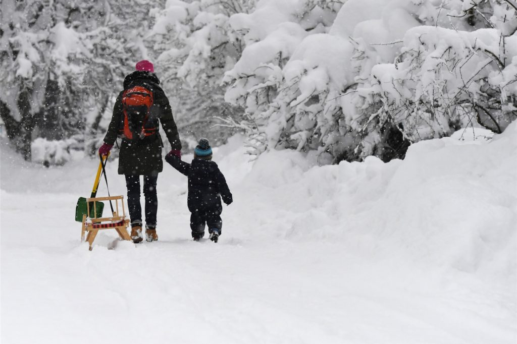 Mutter und Kind mit Schlitten im Schnee