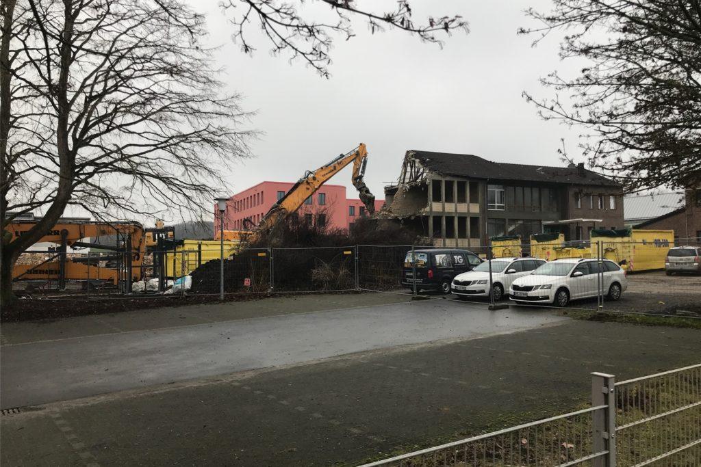 Riesige Abriss-Bagger knabbern am Gebäude der alten Hauptschule in Westerfilde. Das gibt den Blick frei auf den Neubau, der im Sommer zur Gesamtschule wird.
