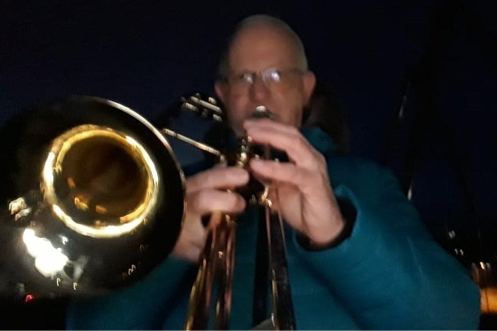 Bernd Kampmann spielt bei Dunkelheit auf der Halde in Derne auf seiner Posaune