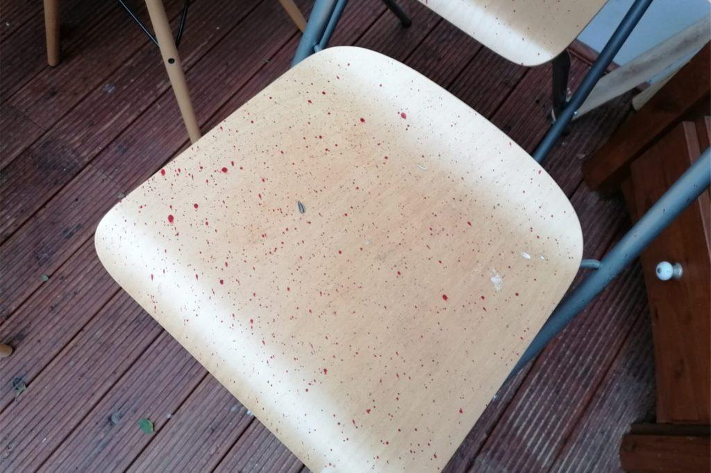 Mehrere Stühle auf der Terrasse sind mit Blutspritzern übersät.
