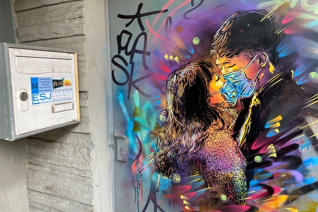 Liebe mit Mundschutz zeigt dieser unbekannte Streetart-Künstler in Frankreich.
