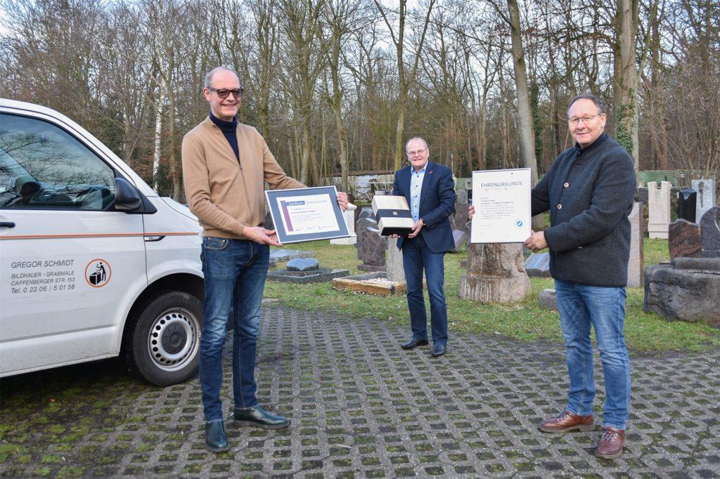 Obermeister Frank Asbeck (r.) und Geschäftsführer Ludgerus Niklas (M.) von der Bildhauer- und Steinmetz-Innung Dortmund und Lünen gratulieren Gregor Schmidt zum 125-jährigen Bestehen seines Unternehmens.