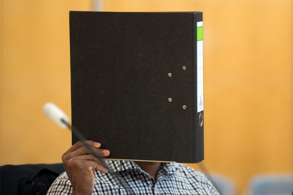 Der 27-Jährige aus Werne, hier hinter einem Aktenordner, war wegen sechsfachen Mordes angeklagt und soll als 15-Jähriger in Sri Lanka vor einem Konvoi der sri-lankischen Armee eine Bombe ferngezündet haben. Wahrscheinlich eine Lüge, wie sich im Prozess herausstellte.
