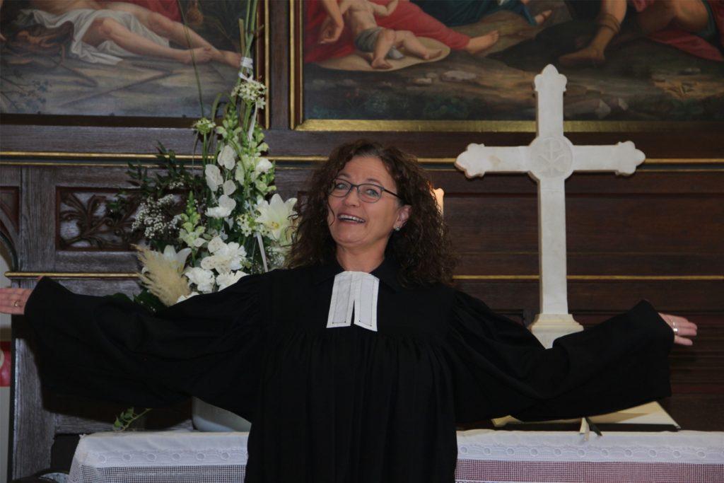 Birgit Leimbach als Pfarrerin im Talar am Altar. Die Begeisterung für ihren Traumberuf sieht man ihr an.