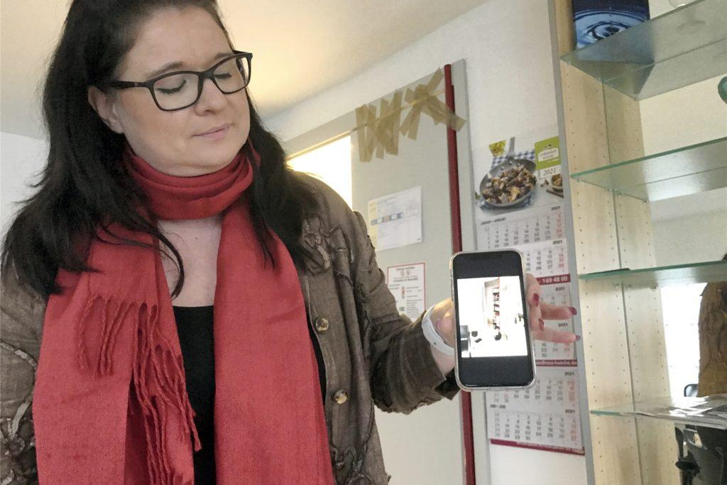 Sandra Loppach, Sekretärin bei der Pflege mit Herz GmbH in Rauxel/Bladenhorst, zeigt auf dem Smartphone einen durchwühlten Schrank. Hinter ihr sieht man eine defekte Tür, die bald repariert werden soll.