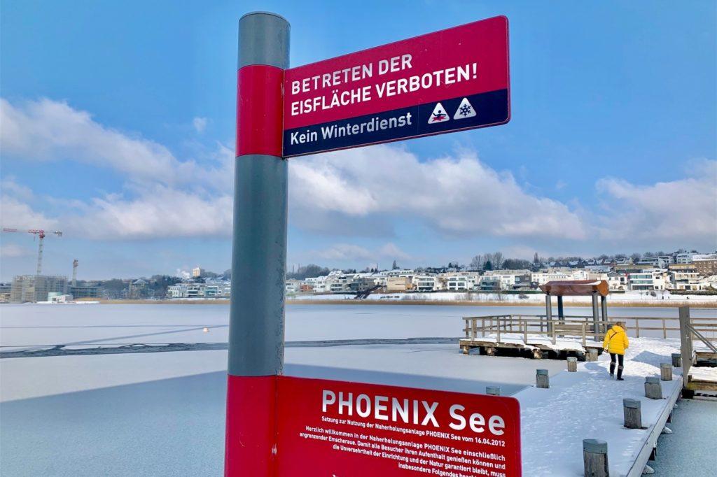 Rund um den See hängen Schilder, die das Betreten der Eisfläche verbieten.