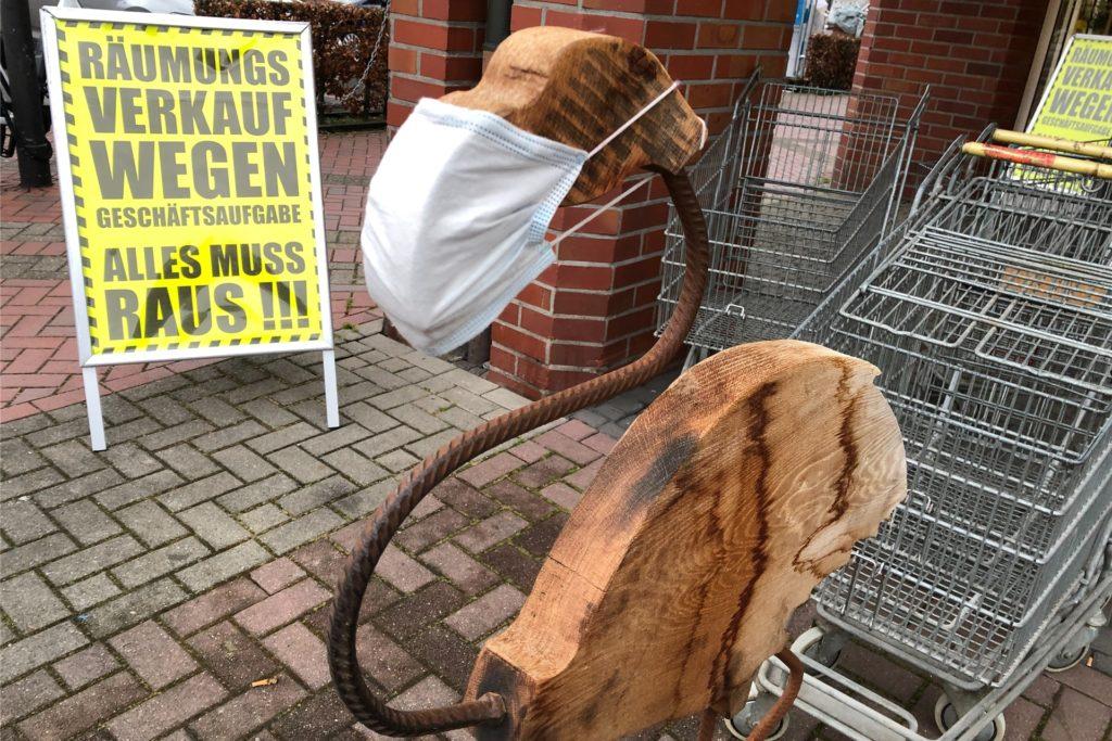 Mit Humor in den Räumungsverkauf zu Corona-Zeiten: Ein hölzerner Flamingo vor der Ladentür trägt einen Mund-Schnabel-Schutz.