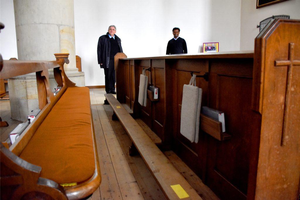 Pastor Stefan Scho (l.) und Pater Raju Peter im Mai bei einem Besuch der Redaktion in der Vituskirche: Die Sitzplätze in den Kirchenbänken sind mit gelben Klebestreifen markiert. Abstand halten ist Pflicht bei den Gottesdiensten.