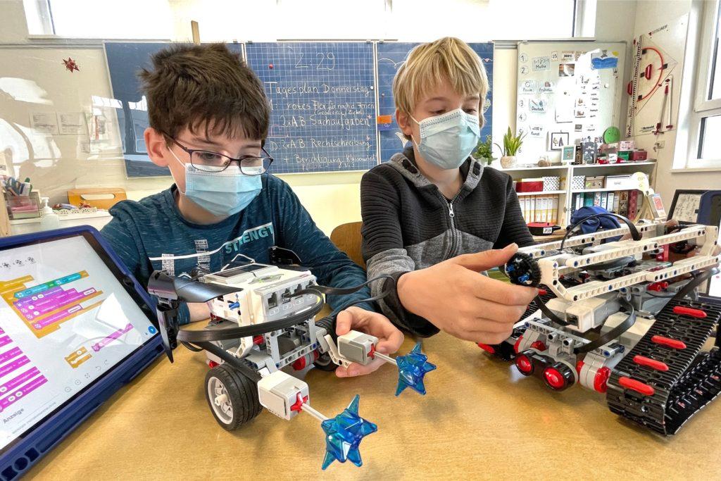 Mit dem Ipad können die Kinder ihren Robotern unterschiedliche Kommandos geben und sie programmieren.
