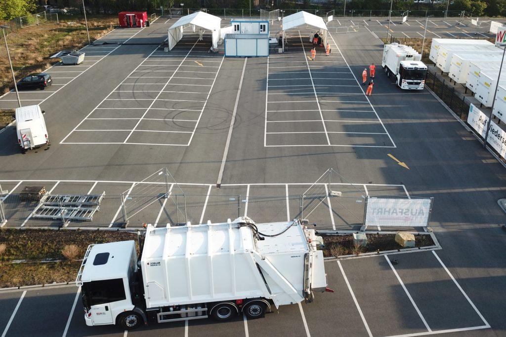 Die Müllwagen mit den großen Aufbauten fahren nicht durch die Zelte. Sie werden abgestellt, dann geht es zu Fuß zum Abstrich.