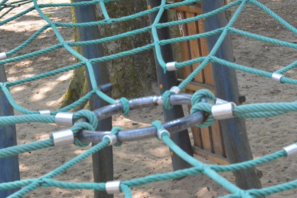Mit einer schwarzen Plastikkappe ist das gerissene Ende eines Seils in diesem Spinnennetz abgedeckt.