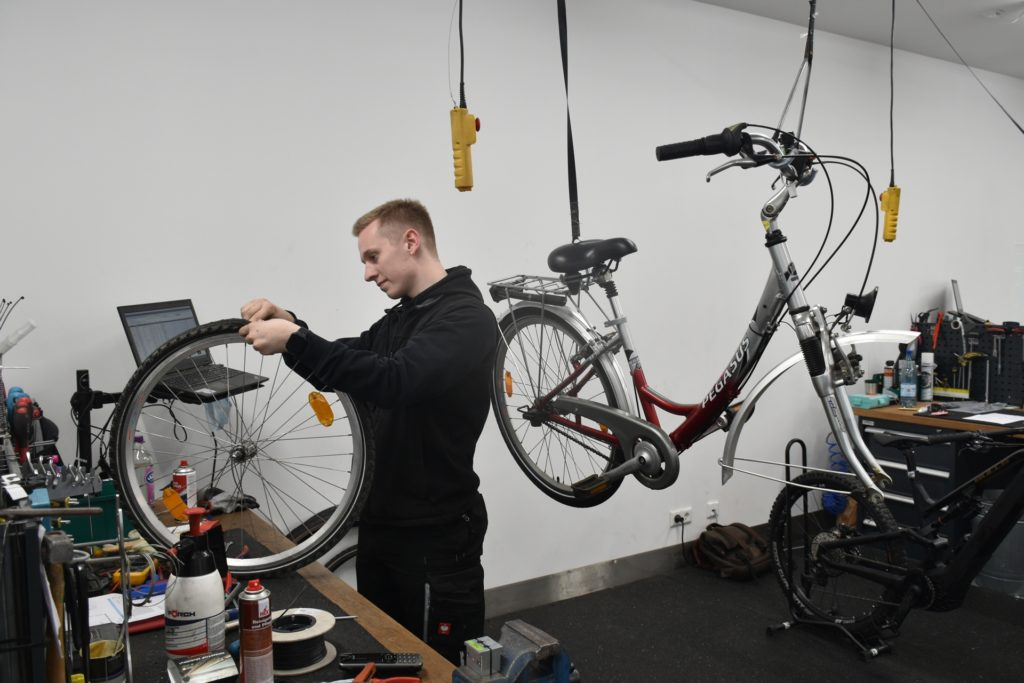 Der Auszubildende Luke Seidel repariert in der Werkstatt von Schmitz ein Fahrrad. Einige Reparaturarbeiten verzögern sich wegen der fehlenden Teile.