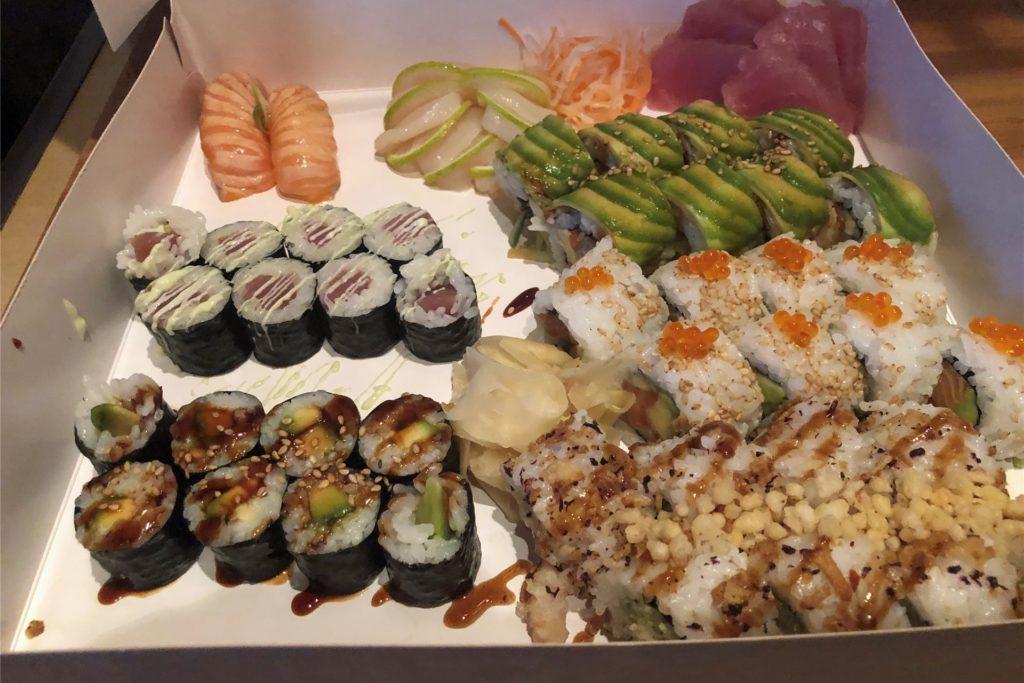 In einer großen Pappbox kommen die verschiedenen Sushi. Der Tunfisch in der rechten hinteren Ecke ist beim Transport etwas zusammengerutscht.