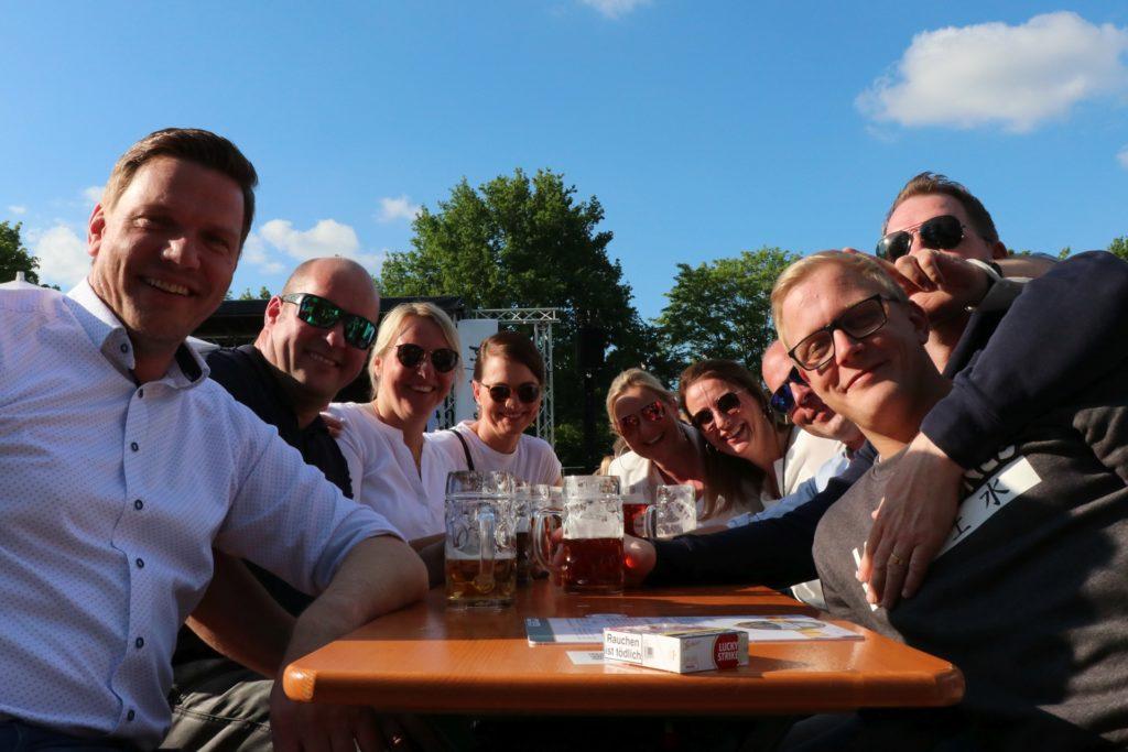 Diese vier Geschwister und ihre Partner genießen das Bier unter blauem Himmel beim Bahnbiergarten.