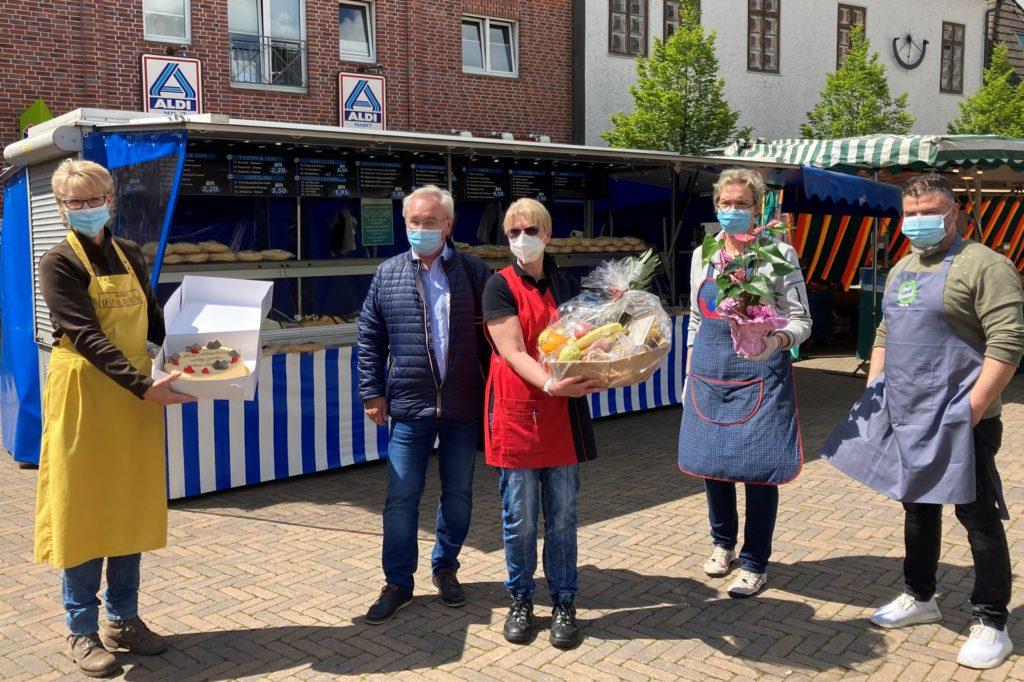 Die Überraschung ist gelungen: Die Olfener Händler überraschen Marktmeister mit Torte, Blümchen und Geschenkkorb.