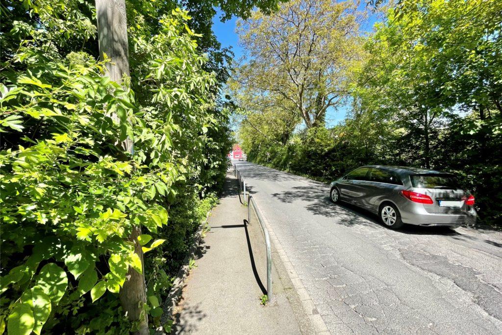 Enge Straße und ein zugewachsener Gehweg: An der Aplerbecker-Mark-Straße muss etwas getan werden, fordern Eltern.