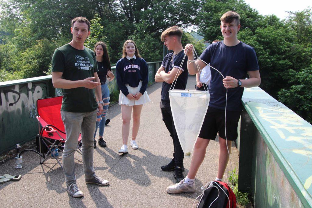 Lehrer Marius Gregg (li.) mit Schülern auf der Lippebrücke. Sie haben mit einem Netz in der Lippe Algen gefischt, die dsie untersuchen werden.