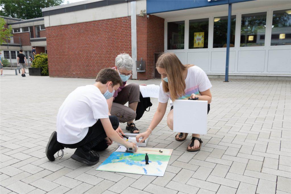 Die beiden Sieger bauen mit ihrer Projektkoordinatorin Ute Schinke das handgemachte Spielbrett auf.