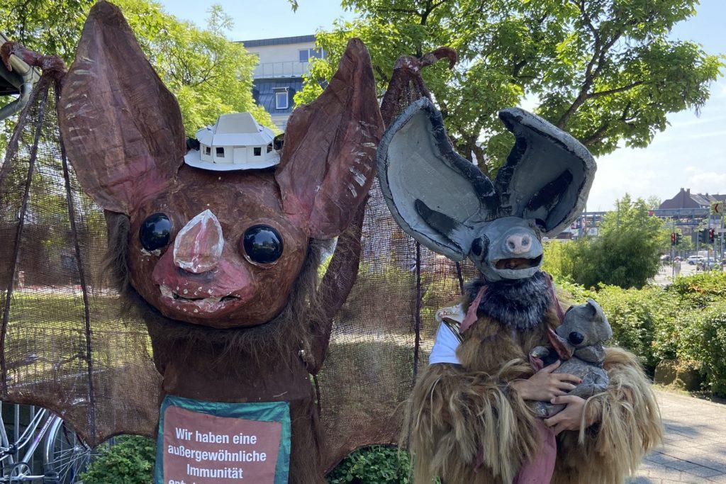 """Am """"Futurology Kiosk"""" informiert Mica (r.) über Besonderheiten von Fledermäusen, etwa über ihre Superimmunität."""