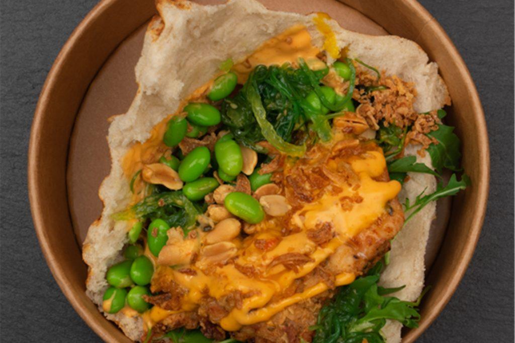 In einem Fladenbrot werden Hähnchen und verschiedene Toppings serviert.