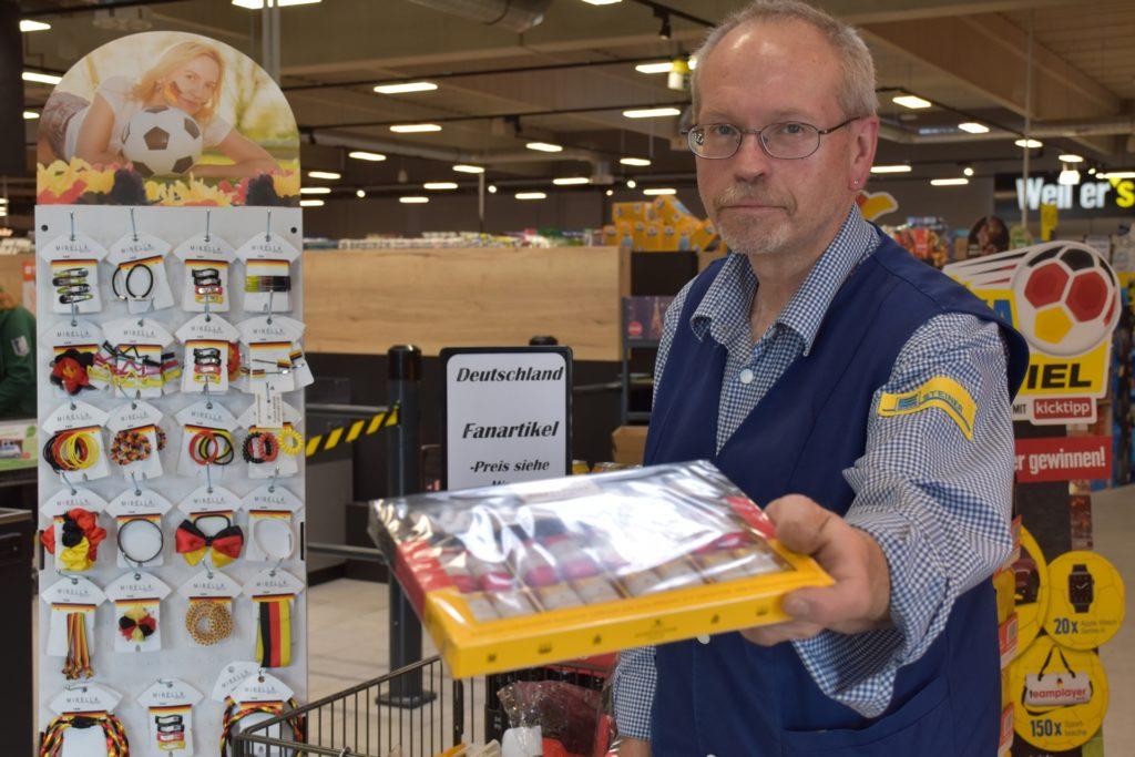 Die typischen Fanartikel, wie Bälle und Schminke sind bereits ausverkauft. Bernd Horn, Filialleiter des Edeka Markts in Legden, hat aber noch weitaus mehr Fanartikel parat.