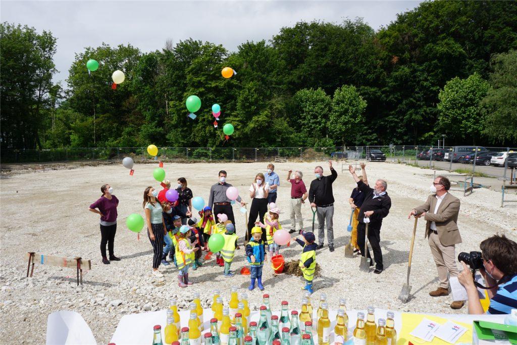 Alle Beteiligten lassen Ballons fliegen, an die Zettel mit guten Wünschen geheftet sind.