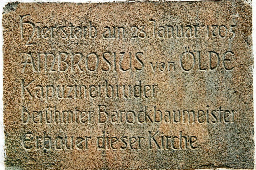 Inschrift an der Klosterkirche, die auf den Baumeister Ambrosius von Oelde verweist, der die Kirche zwischen 1677 und 1681 errichten ließ.