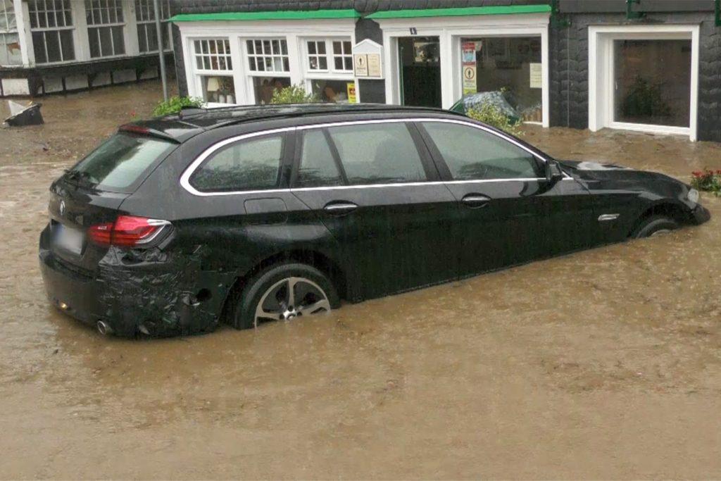 Ein Auto steht auf einer überfluteten Straße in Solingen.