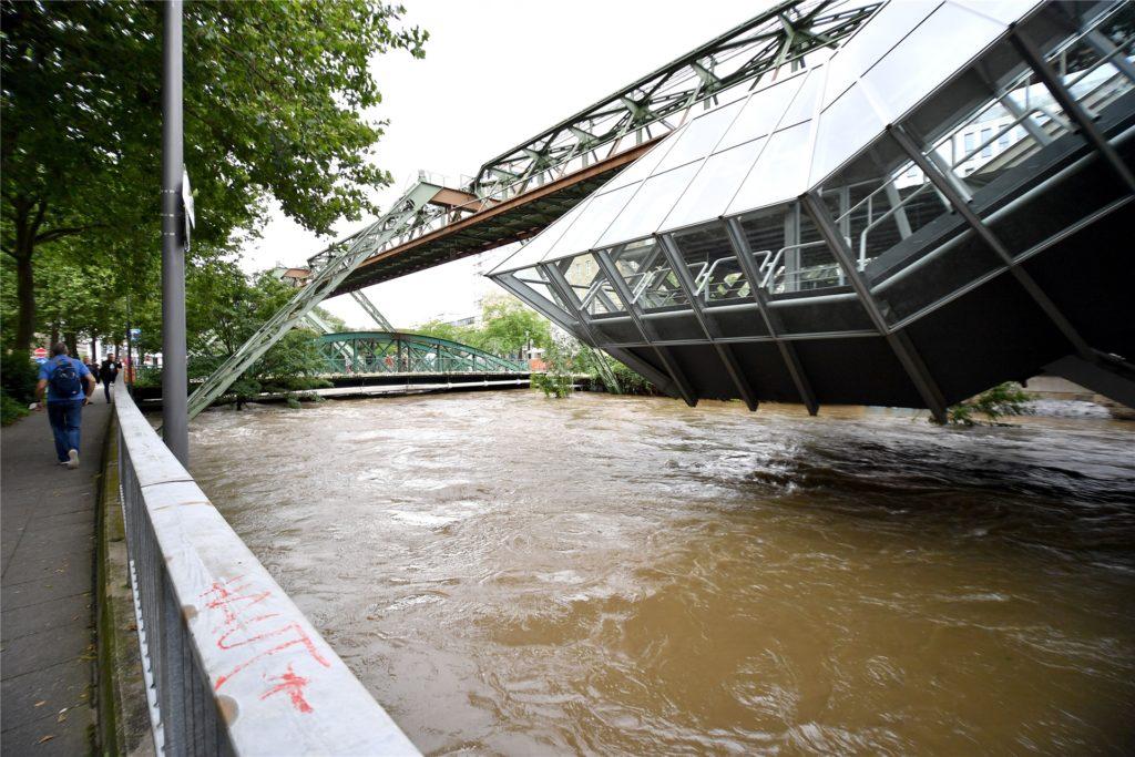 Blick auf die überflutete Station der Schwebebahn in der Pestalozzistraße über der Wupper. Nach dem Unwetter mit sintflutartigen Regenfällen in NRW laufen die Aufräumarbeiten.