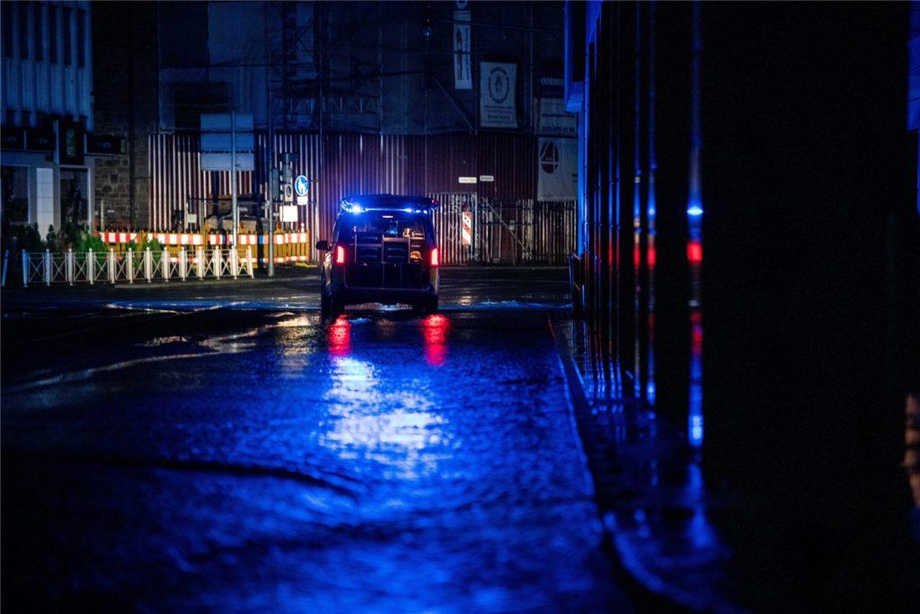 Ein Einsatzwagen der Polizei sichert eine überflutete Straße. Die Wupper in der Wuppertaler Innenstadt tritt über das Ufer.