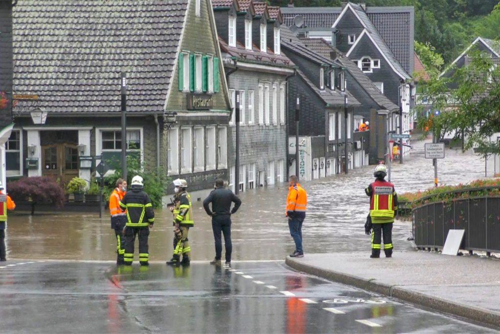 Einsatzkräfte stehen an einer überschwemmten Straße.