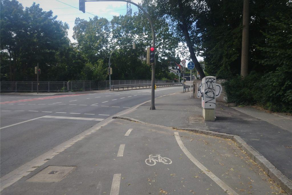 Auf der einen Seite ist der Radweg rot markiert - die gegenüberliegende Straßenseite ist indes bis zum Beginn der Kreuzung weiß umrandet. Danach weist lediglich ein Schild auf den geteilten Fuß- und Gehweg hin.