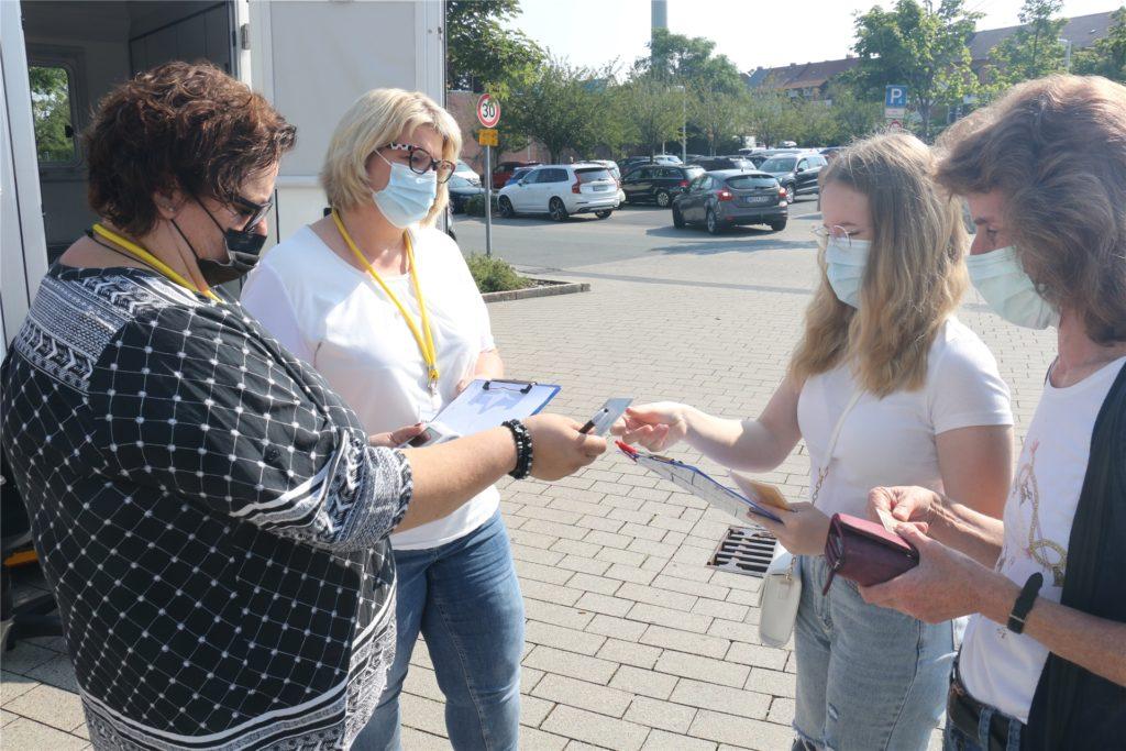 Vor der Impfung zeigt Sarah Tönjann ihren Ausweis und die Versichertenkarte vor.