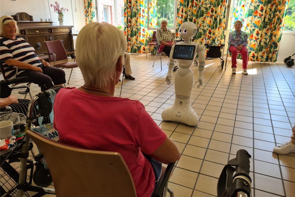 Der Roboter schaut die Bewohnerinnen und Bewohner mit runden Kulleraugen an.