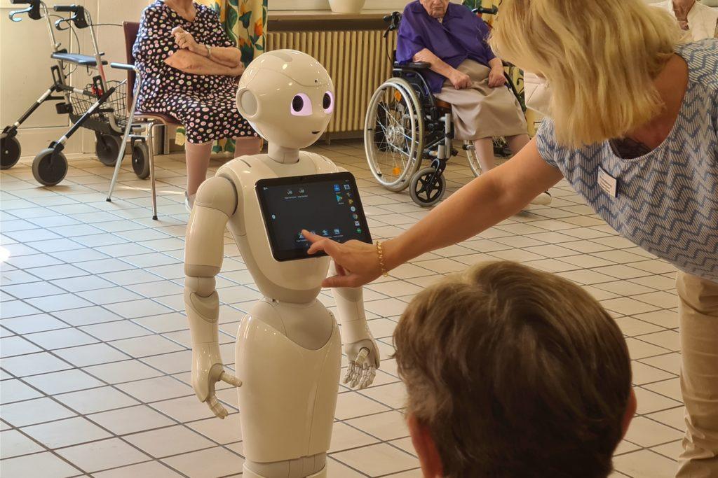 Nicole Wähning, Koordinatorin Sozialer Dienst im Evangelischen Altenzentrum Lünen, bedient Pepper über einen integrierten Tablet-PC. Sie kann einstellen, welche Handlungen der Roboter durchführen soll.