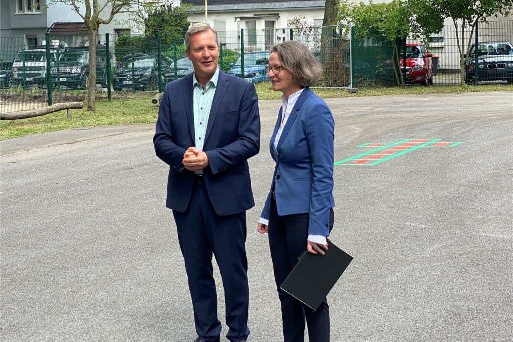 Bürgermeister Jürgen Kleine-Frauns (l.) hat den Förderbescheid von Ministerin Ina Scharrenbach auf dem Schulhof der Viktoriaschule entgegengenommen.   Foto: Stadt Lünen.