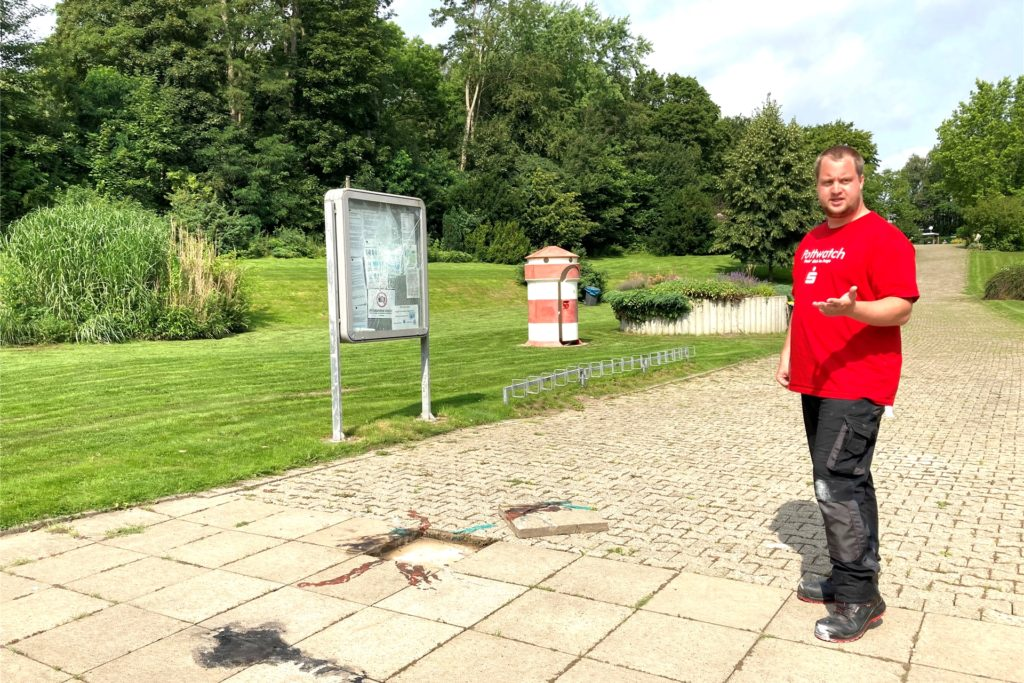 Christian Rumpel, stellvertretender Badleiter, zeigt die Brandflecken auf den Bodenplatten vor dem Schwimmbecken.
