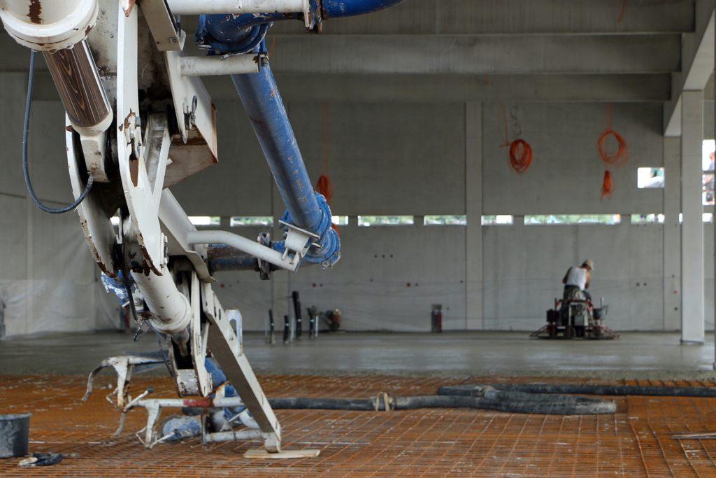 Die Pumpe lenkt über Schläuche den Beton genau dorthin, wo er benötigt wird. Im Hintergrund wird die Platte bereits bearbeitet und geglättet.