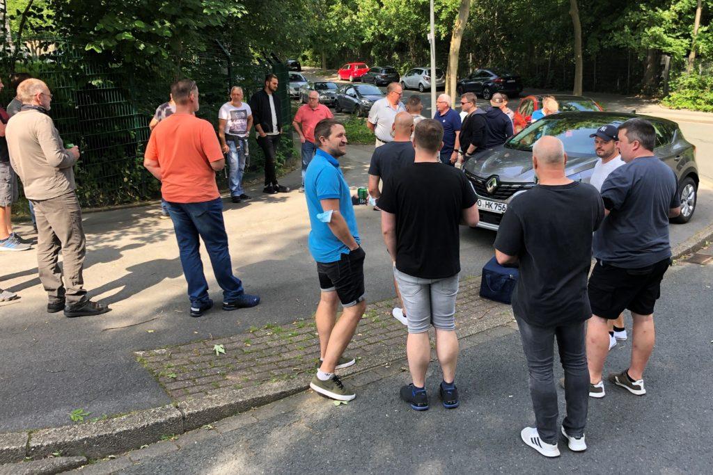 Verabschiedung auf dem Bürgersteig: Fernab von der videoüberwachten Zufahrt zum Caterpillar-Gelände traf sich nach der letzten Schicht noch ein kleines Grüppchen von Mitarbeitern. So geräuschlos gingen am Freitag (30.7.) 600 Industriearbeitsplätze in Dortmund verloren.