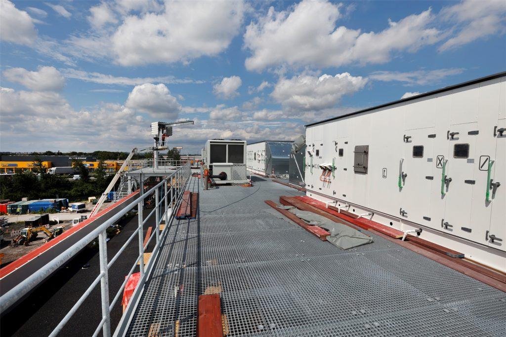 Ein neuer Portalkran wird auf das Dach gehoben. Mit ihm werden künftig  Ersatzteile oder Geräte für Wartungsarbeiten gehoben. Diese dürfen nicht durch die Halle transportiert werden, weil dort unter Reinraum-Bedingungen gefertigt wird.