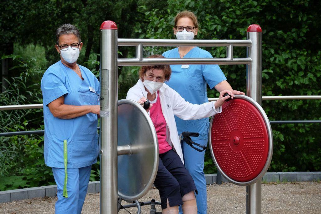 Mitarbeiterinnen der physiotherapeutischen Abteilung des Krankenhauses erläutern einer Nutzerin ein Gerät zur Förderung von Bewegungsanreizen.