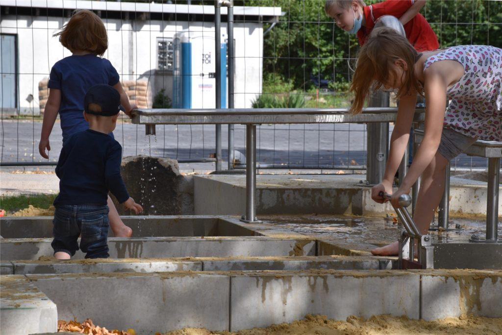Bei 20 Grad spielen die Kinder gemeinsam am Wasser.