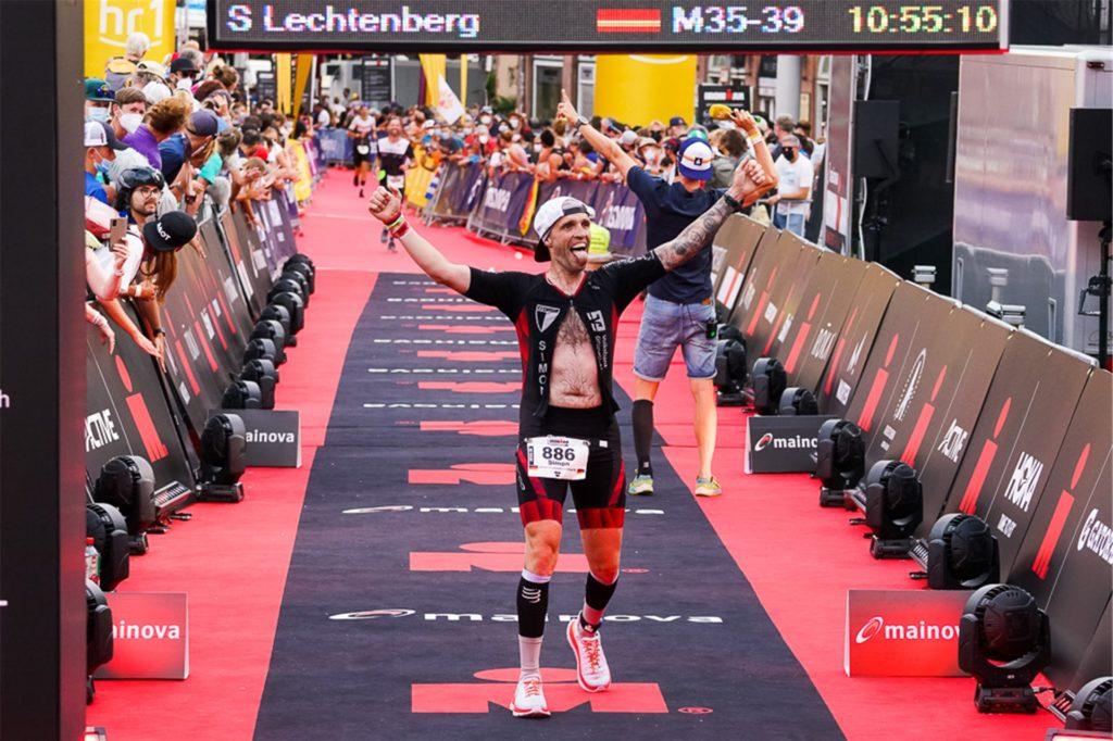 Simon Lechtenberg feiert seine gute Gesamtzeit von 10:55:10 Stunden.