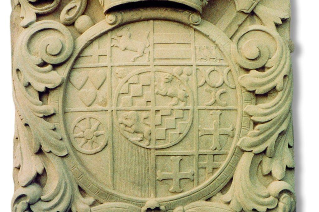 Detailabbildung des Sandsteinwappens von 1729, geschaffen vom Ahauser Bildhauer Bernhard Vagezer: Im Mittelpunkt steht das Wappen des Fürstbischofs von Münster, Clemens August von Bayern.