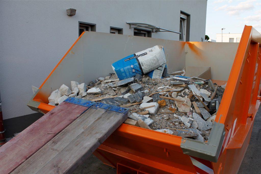 Hier geht die Baustelle wieder von vorne los: Zwei orangene Container stehen momentan vor dem Haus der Familie. Der Boden musste inklusive des Estrichs entfernt werden.