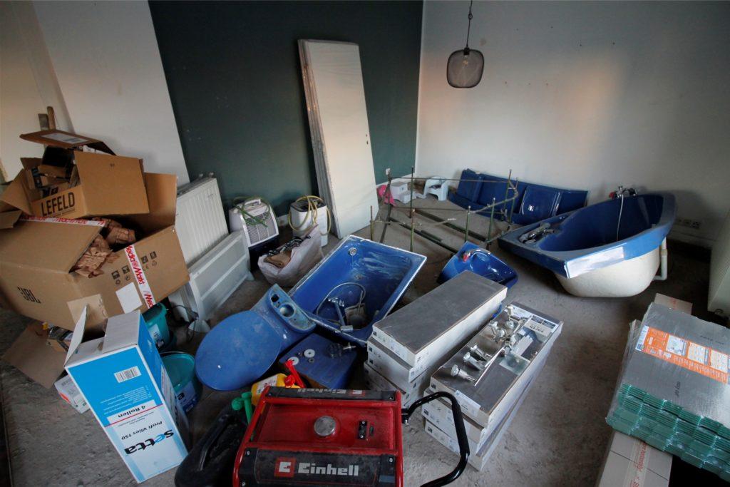 Das Wohnzimmer dient aktuell als Zwischenlager. Auch hier fehlt der Holzboden. Die Feuerwehr hatte das Wasser abgepumpt, allerdings war die Heizung in Mitleidenschaft gezogen worden und Öl ausgelaufen. Das verschmutzte Wasser war durch die Feuerwehrschläuche auf den Wohnzimmerboden gelangt.