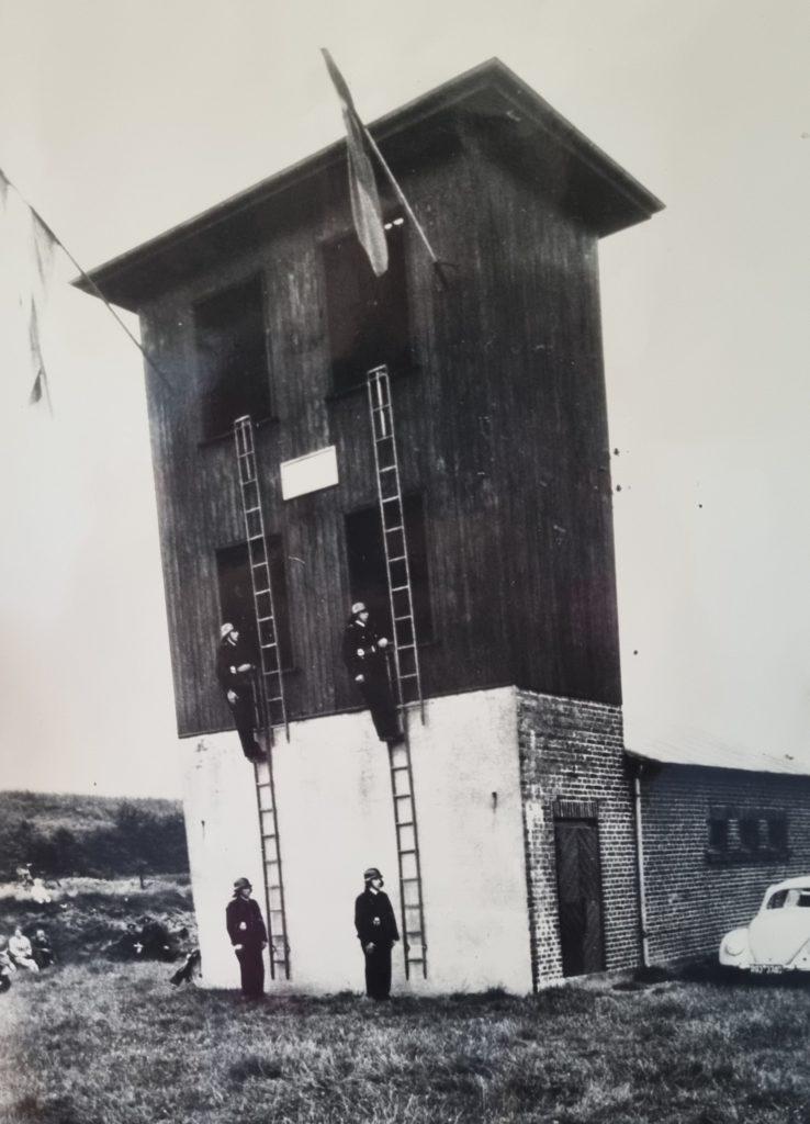 Feuerwehrleute bei einer Leiterübung am alten Steigeturm um 1956, wo heute die Rettungswache der Lavesumer Löscheinheit steht.
