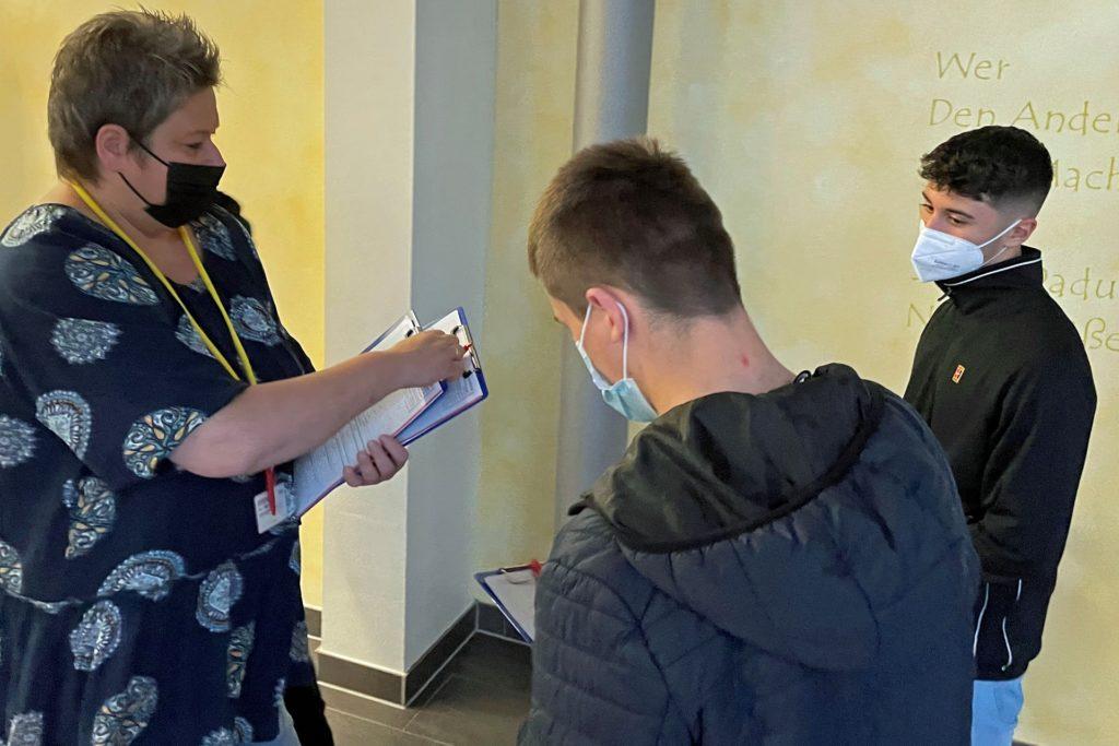 Alexandra Grengel-Doennges vom Impfzentrum Unna verteilt an die wartenden Schüler des Berufskollegs die auszufüllenden Bögen.