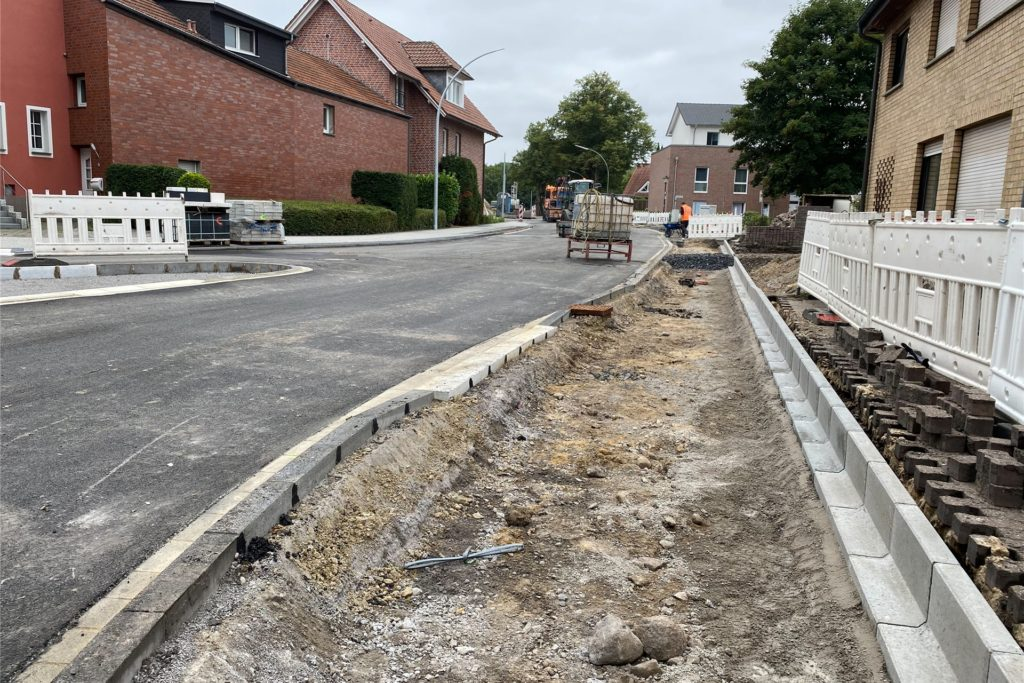 Die Fußgängerwege werden mit weißen Steinen gepflastert - das geschieht als einer der letzten Schritte, damit die Steine von den Baustellenfahrzeugen nicht verschmutzt werden.